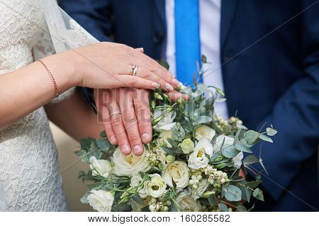 hands of the bride and groom at a wedding bouquet.