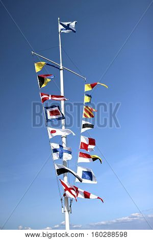 Marine flags of different countries on a mast on blue sky background