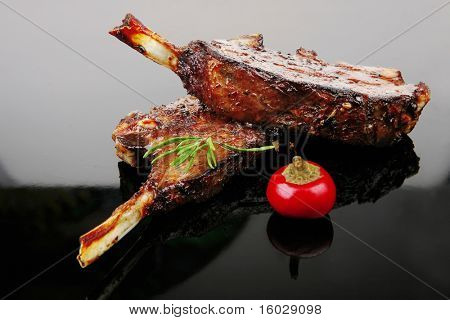 savory plate: grilled ribs over black with spices and hot pepper