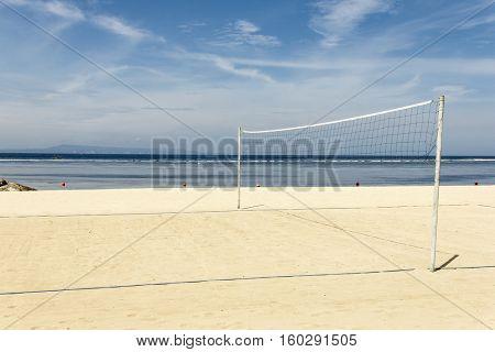 Volleyball net on empty sand beach sunny day. Bali, Indonesia