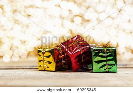 Multicolored shiny boxes of gifts on a festive background with bokeh