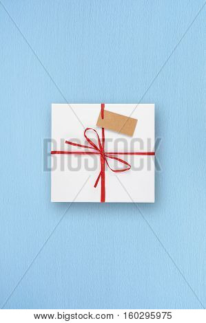 White gift box with blank tag on blue table