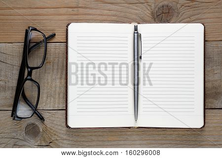 Notebook pen and glasses on wooden table top view