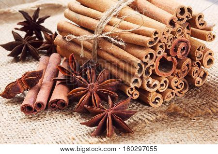 star anise and cinnamon sticks in a bunch on a burlap background