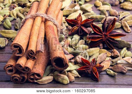 cardamom star anise and cinnamon sticks in a bunch on a wooden striped background