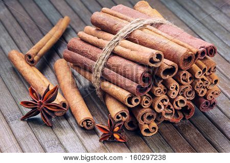 star anise and cinnamon sticks in a bunch on a wooden striped background