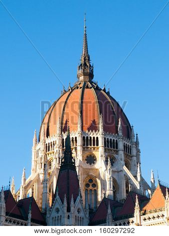 Detailed view of historical building of Hungarian Parliament, aka Orszaghaz, with typical central dome on clear blue sky background. Budapest, Hungary, Europe. It is notable landmark and seat of the National Assembly of Hungary. UNESCO World Heritage Site