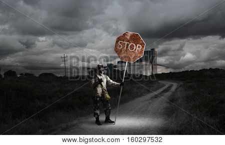 Stalker in gas mask with precaution stop signboard
