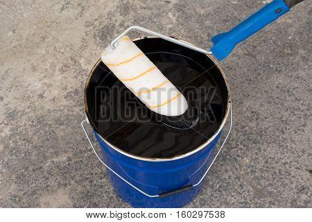 Waterproofing. Roller brush. Worker covered surface bitumen primer. Tools for waterproofing. Waterproofing primer.