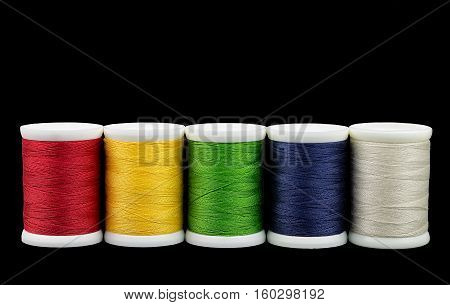 Coil colored nylon thread on a isolated black background. Several spools of colored thread on a black background