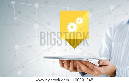 Hands of businessman showing tablet with gear icon on screen