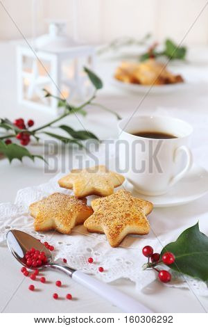 Homemade Christmas cookies cup of coffee holly and burning lantern