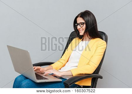 Young pretty woman wearing eyeglasses and dressed in yellow jacket sitting on office chair while using laptop over grey background.