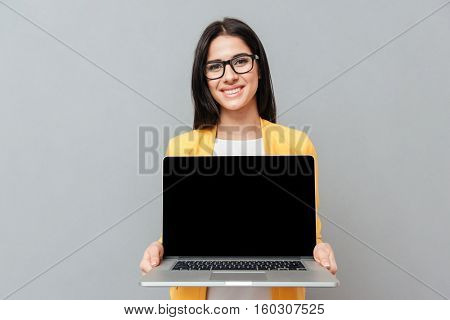 Pretty woman wearing eyeglasses and dressed in yellow jacket showing laptop display to camera over grey background.