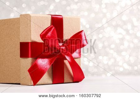 Present box with red bow on silver sparkling background. Festive concept for Christmas