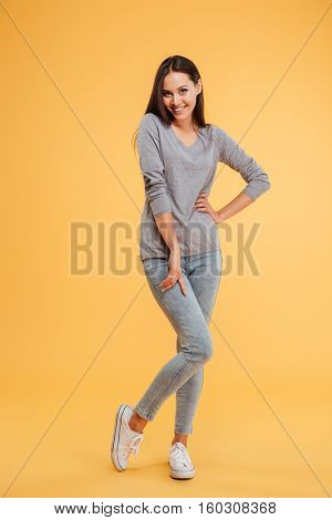 Full length young shy woman in studio. isolated orange background