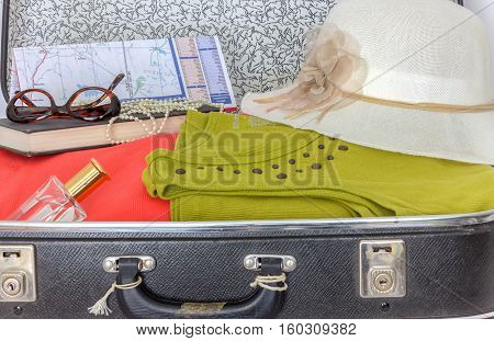 horizontal image of a black suitcase full of ladies clothing along with a road map and glasses and hat ready for a trip.