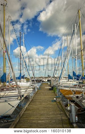 Several sailing boats are moored to the wharf with a mole on the back and with blue cloudy sky. Vertical orientation.