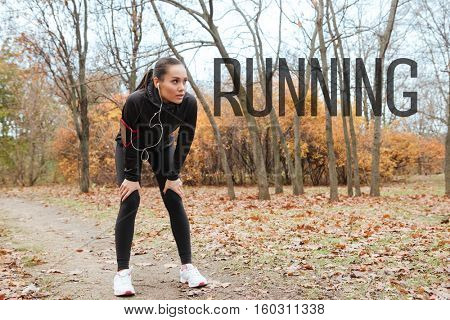 Exhausted runner in warm clothes with headphone in autumn park. Full length image. Running!