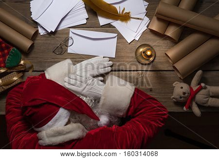 Santa Claus sitting at his room at the table and sleep after hard day