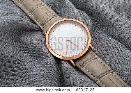 Gray band wrist watch on gray silk fabric background