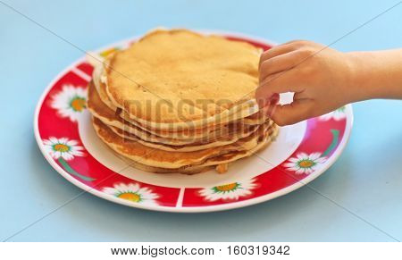 Child hand and pancakes in plate. Shallow depth-of-field