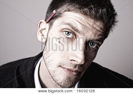 Portrait Of Thoughtful Young Business Man With Pencil