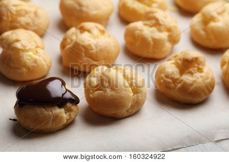 Rows of Profiteroles with chocolate glaze on a baking paper