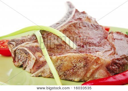 savory : roasted beef spare rib on green dish with cutlery thyme pepper and tomato isolated over white background