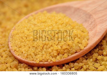 brown sugar heap and on wooden spoon