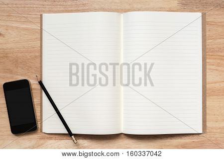 Top view of open notebook with two blank pages pencil and smart phone on wooden table