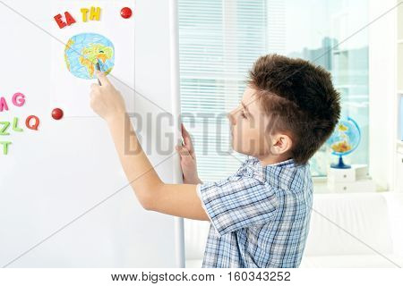 Little kid pointing at drawn earth on whiteboard