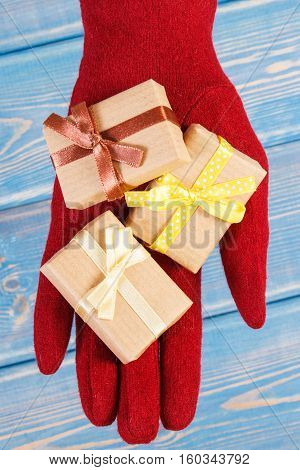 Hand Of Woman In Gloves With Gifts For Christmas Or Other Celebration