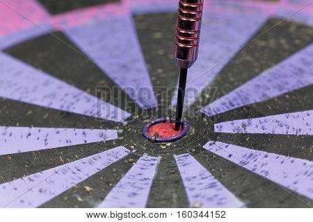 Macro of dart arrow in an old dartboard.
