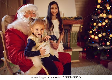 Happy little girl in Santa Claus lap, merry Christmas