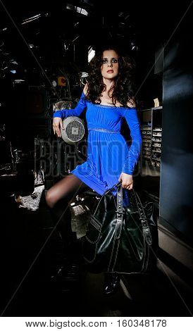 Brunette wearing a blue dress and carrying a black bag posing in an old factory beside a huge machine with motors