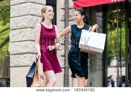 Fun happy young women out shopping together carrying their purchases in bags with smiles of satisfaction as they walk down the street