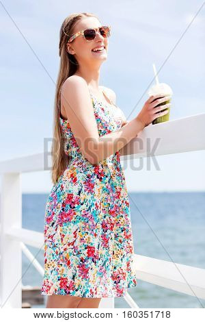 Beautiful young woman with sunglasses drinking green vegetable smoothie.