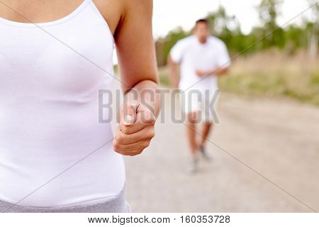 two people running down the road in countryside