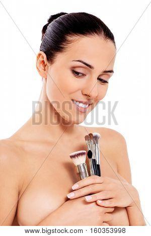 Beautiful girl with make-up brushes. Isolated on white.