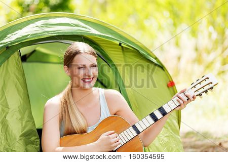 Young woman playing the guitar in a tent on the nature
