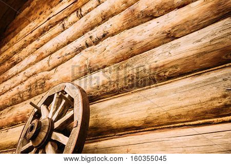 Wooden wheel on the wall of the log house