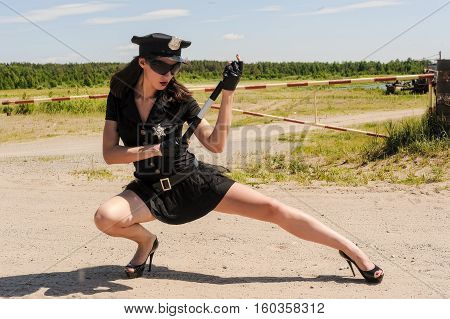 Young beautiful police woman standing on rural road
