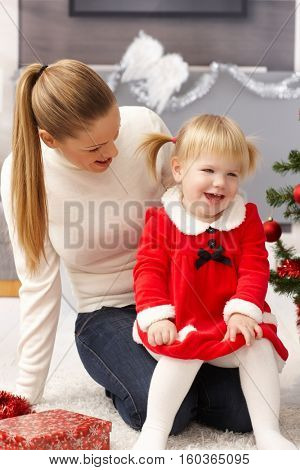 Mother and daughter smiling happy at christmas time.