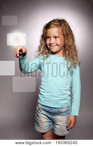 Child clicks on the display screen. Girl press screen computer