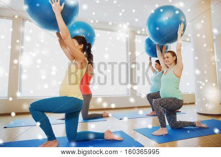 pregnancy, sport, fitness, people and healthy lifestyle concept - group of happy pregnant women exercising with stability ball in gym over snow