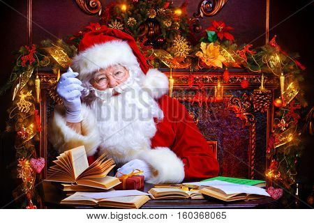 Good old Santa Claus in his house sitting next to the fireplace and Christmas tree ready for Christmas.