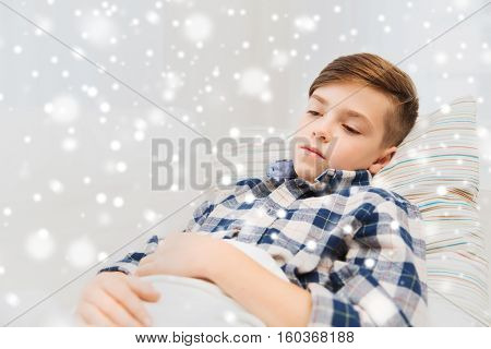 childhood, healthcare, people and medicine concept - ill boy with flu lying in bed at home over snow