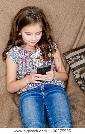 Cute little girl with mobile phone sitting on the sofa technology and internet concept