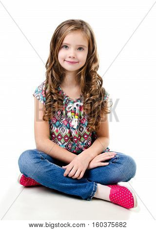 Adorable smiling little girl sitting on a floor isolated on a white
